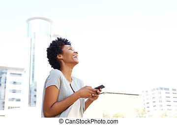 Smiling african woman standing outside holding cell phone