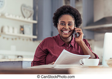 Smiling African woman talking on her cellphone at home