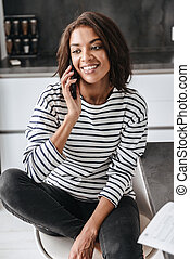 Smiling african woman using mobile phone