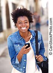Smiling african woman walking outside with cell phone