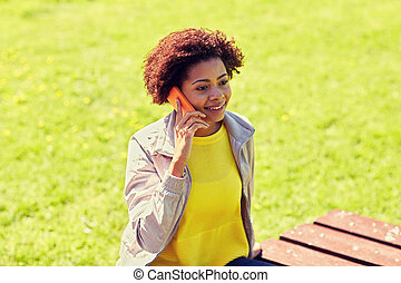 smiling african young woman calling on smartphone