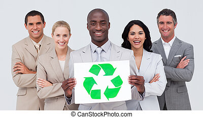 Smiling Afro-American businessman holding a recycle symbol with his team