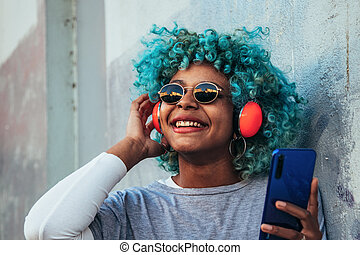 smiling afro american girl with headphones and mobile phone
