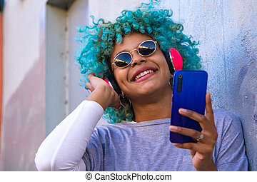 smiling afro american girl with mobile phone and headphones