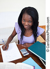 Smiling Afro-American teen girl doing her homework