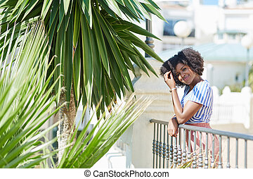 Smiling afro american woman leaning against fence outside