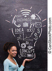 Smiling afro-american woman with painted lightbulb on chalkboard
