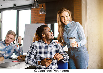 smiling Afro guy in checked T-shirt is looking at shy office worker holding a cup of tea