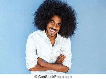 smiling afro man with arms crossed against blue wall