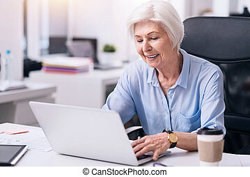 Smiling aged businesswoman working in the office