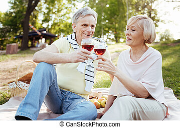 Smiling aged couple enjoying conversation in the park