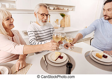 Smiling aged couple enjoying dinner with son at home