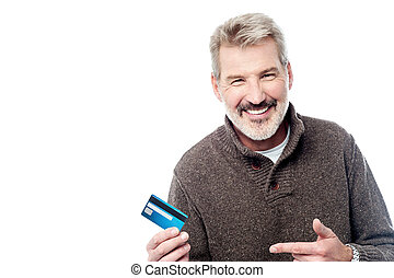 Smiling aged man showing his debit card - Mature man holding...