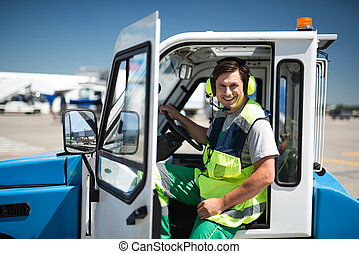 Smiling airport worker sitting in vehicle