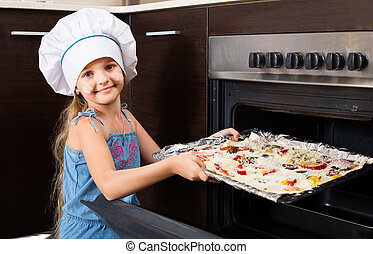girl in cook cap near oven with pizza