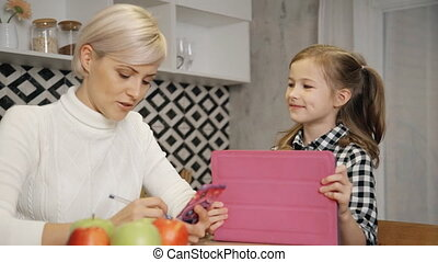 Woman and little daughter spending time with digital tablet...
