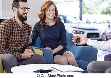 Smiling and happy marriage buying new car in exclusive showroom