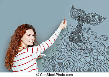 Smiling artist holding a brush and painting a big whale