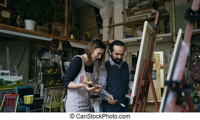 Smiling artist man teaching young girl to draw paintings and explaining the basics in art studio