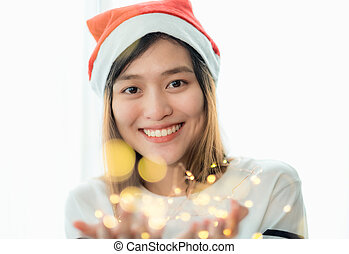 smiling asia woman wear santa hat holding party string...