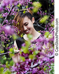 Smiling Asian American Woman Amid Spring Purple Blossoms