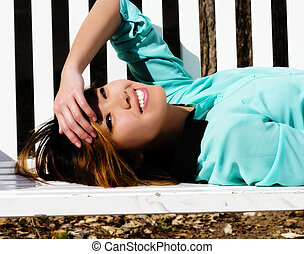 Smiling Asian American Woman Reclining On Bench Outdoors