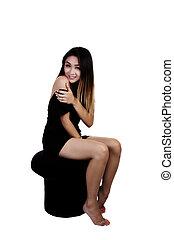 Asian American Woman Sitting On Stool In Black Dress