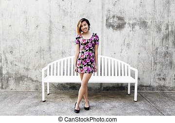Smiling Asian American Woman Standing In Floral Dress