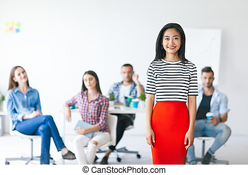 Smiling asian business leader with her team on background