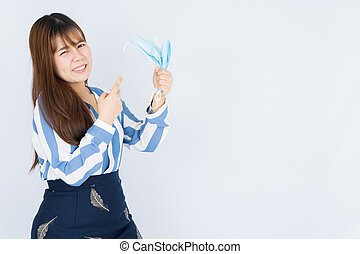 Smiling Asian business woman pointing finger to hand grasping mask over grey background. Back to the normal concept.