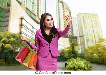 Smiling asian business woman selfie with holding shopping bags