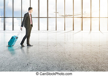 Smiling asian businessman with blue suitcase walking on the airport hall