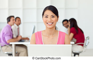 Smiling asian businesswoman at her computer