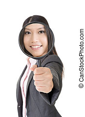 Smiling asian businesswoman holding magnifying glass