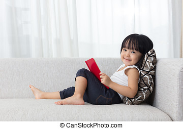 Smiling Asian Chinese little girl reading book on the sofa