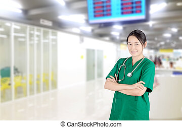 Smiling asian female doctor with stethoscope in hospital hallway