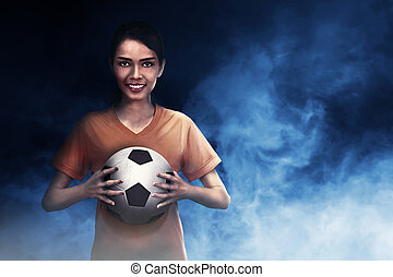 Smiling asian footballer woman carrying ball