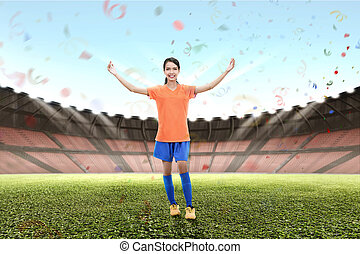 Smiling asian footballer woman celebrate victory
