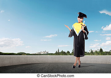 Smiling asian girl in graduation cap and diploma scroll