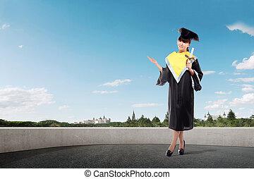 Smiling asian girl in graduation cap and diploma scroll