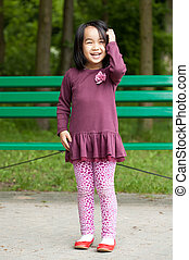 Smiling asian girl in park