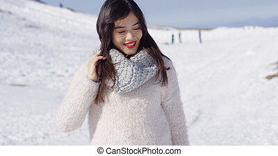 Smiling asian girl in woolen sweater relaxing on snowy slope...