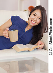 Smiling asian girl lying on the sofa reading a novel and drinking