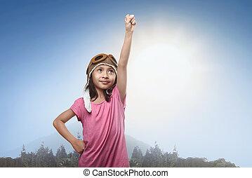 Smiling asian little girl in aviator helmet dreaming of becoming a pilot