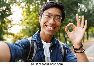 Smiling asian male student in eyeglasses making selfie