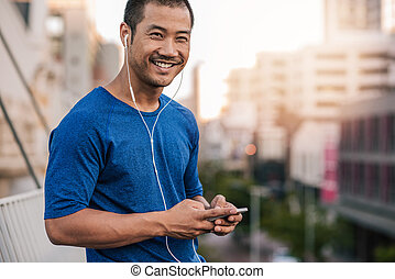 Smiling Asian man preparing a playlist for a city run - ...