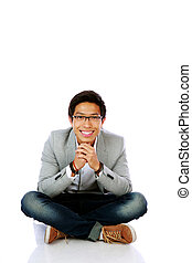Smiling asian man sitting on the floor over white background