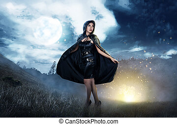 Smiling asian witch woman with black hooded cloak standing