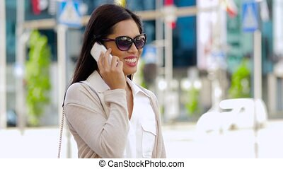 smiling asian woman calling on smartphone in city -...