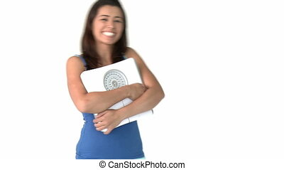 Smiling asian woman holding a scales against a white...